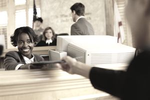 Clerk handing a file to someone in the courthouse