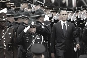 President Obama walking between rows of law enforcement officers saluting him.