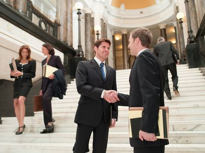 Smiling lawyers shaking hands in front of stairs at a courthouse