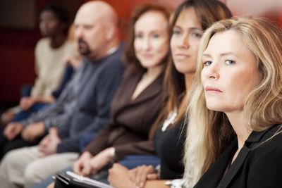 Women and men sit and listen from the jury box during a court proceeding.