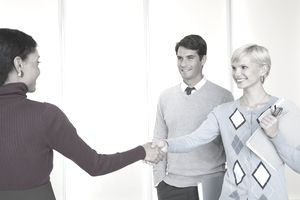 Two businesswomen in office shaking hands with businessman nearby