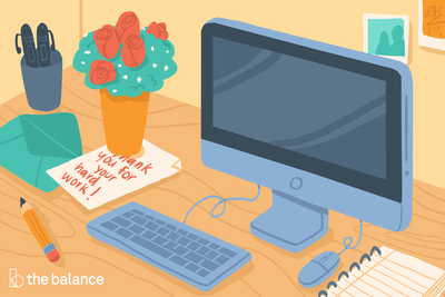 Image shows a desk with a computer, a notebook, a cup with pens, and also a bouquet of flowers over a note that reads