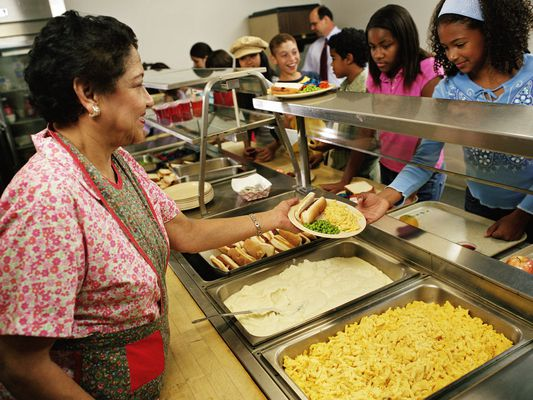 Mature woman serving food to students (12-14) in cafeteria