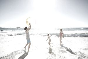 Family playing with ball by the ocean.