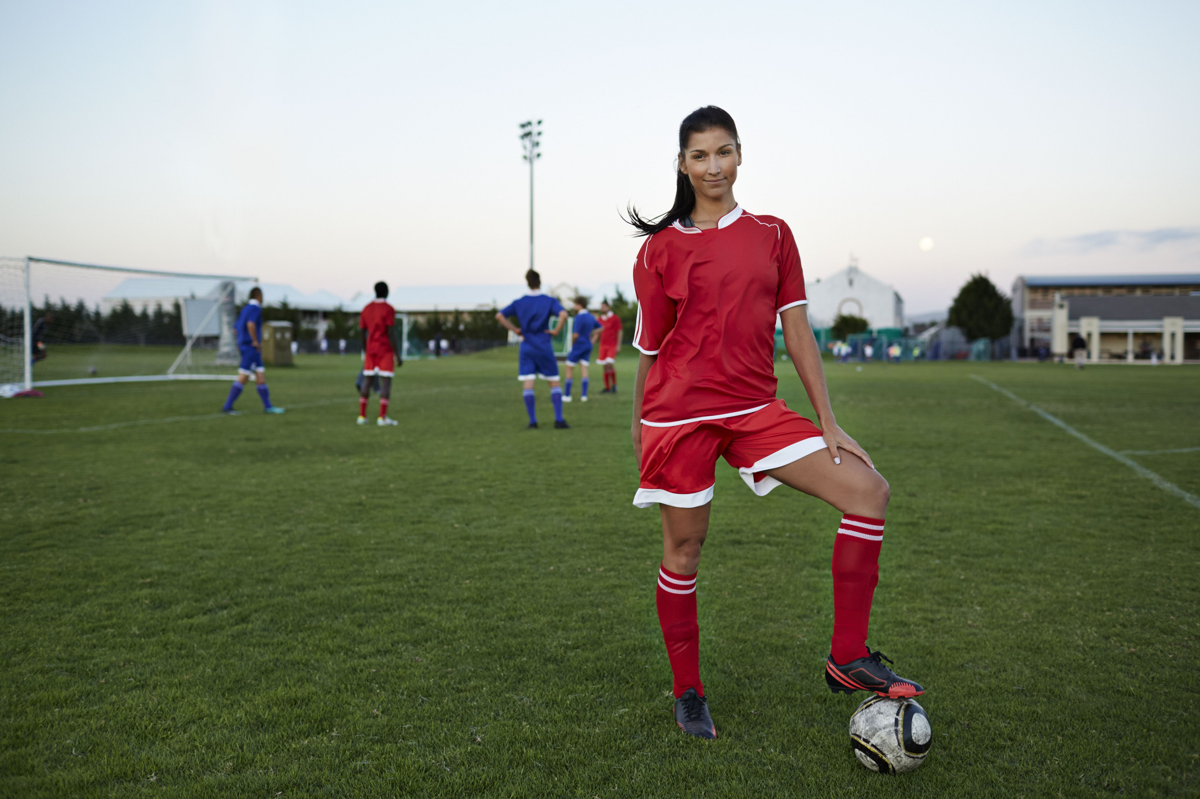 Female soccerplayer standing with foot on the ball