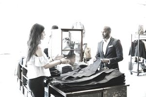 Shopkeeper explaining a selection of denim to customer in mens clothing boutique