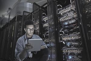 IT Technician Using Digital Tablet in Dark Server Room