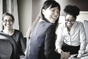Three smiling businesswomen working in hotel suite