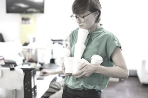 Unpaid intern struggling to carry several coffee cups to office workers.