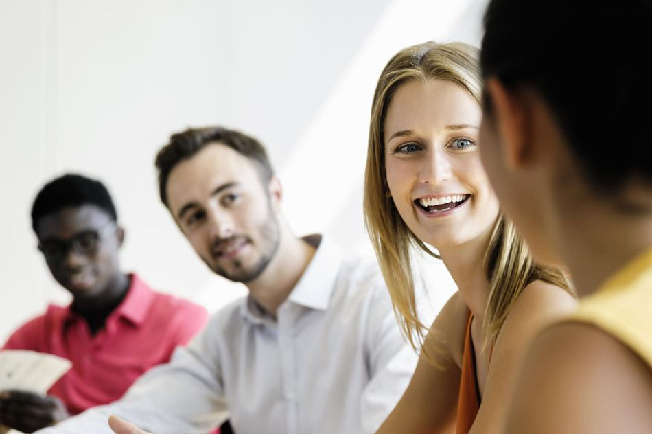 Coworkers discussing plans in office, smiling