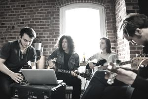 Band composing a new song in a studio