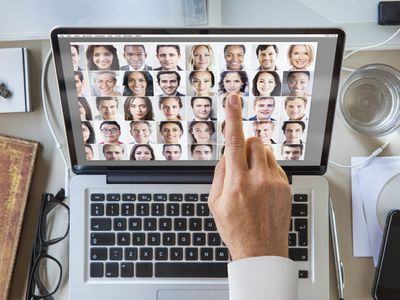 a man working on a laptop with pictures of various different faces on the screen