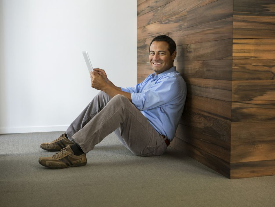 A man sitting against a wall with a tablet