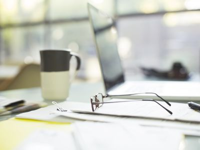 Close up of coffee cup and eyeglasses on paperwork near laptop