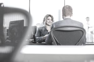 Woman and man talking at desk in office during employee evaluation