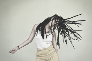 Shot of an attractive young woman dancing against a green background