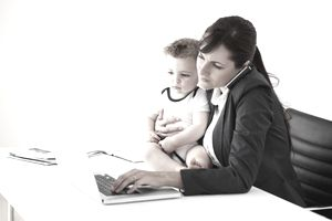 A business woman holds a baby at work