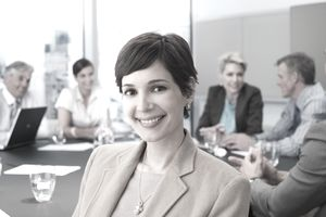 a young woman sitting with a group of co-workers in a conference room