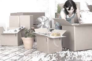 Woman unpacking cardboard boxes after relocating for a job.