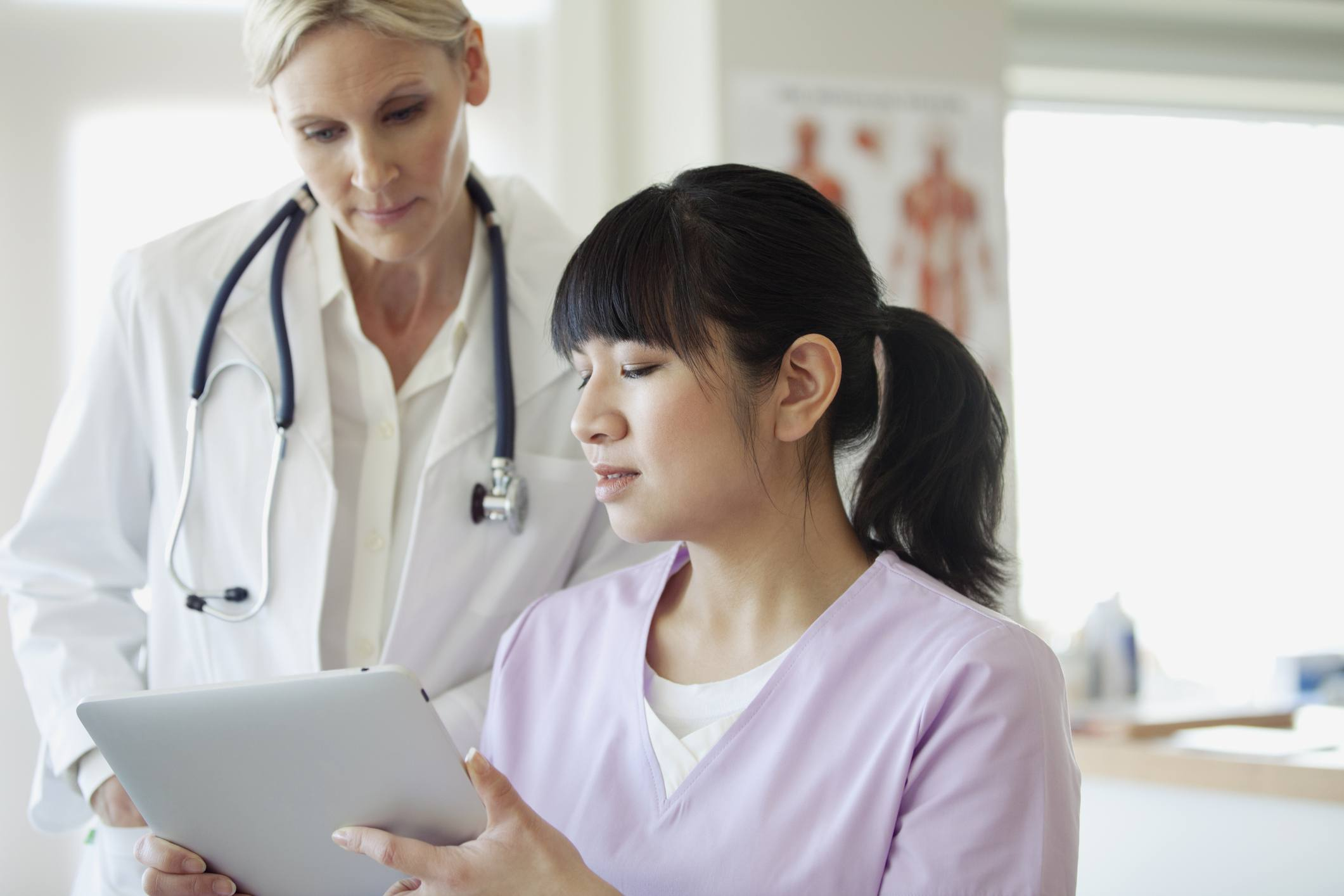 Physician reviewing information on a tablet with a physician assistant