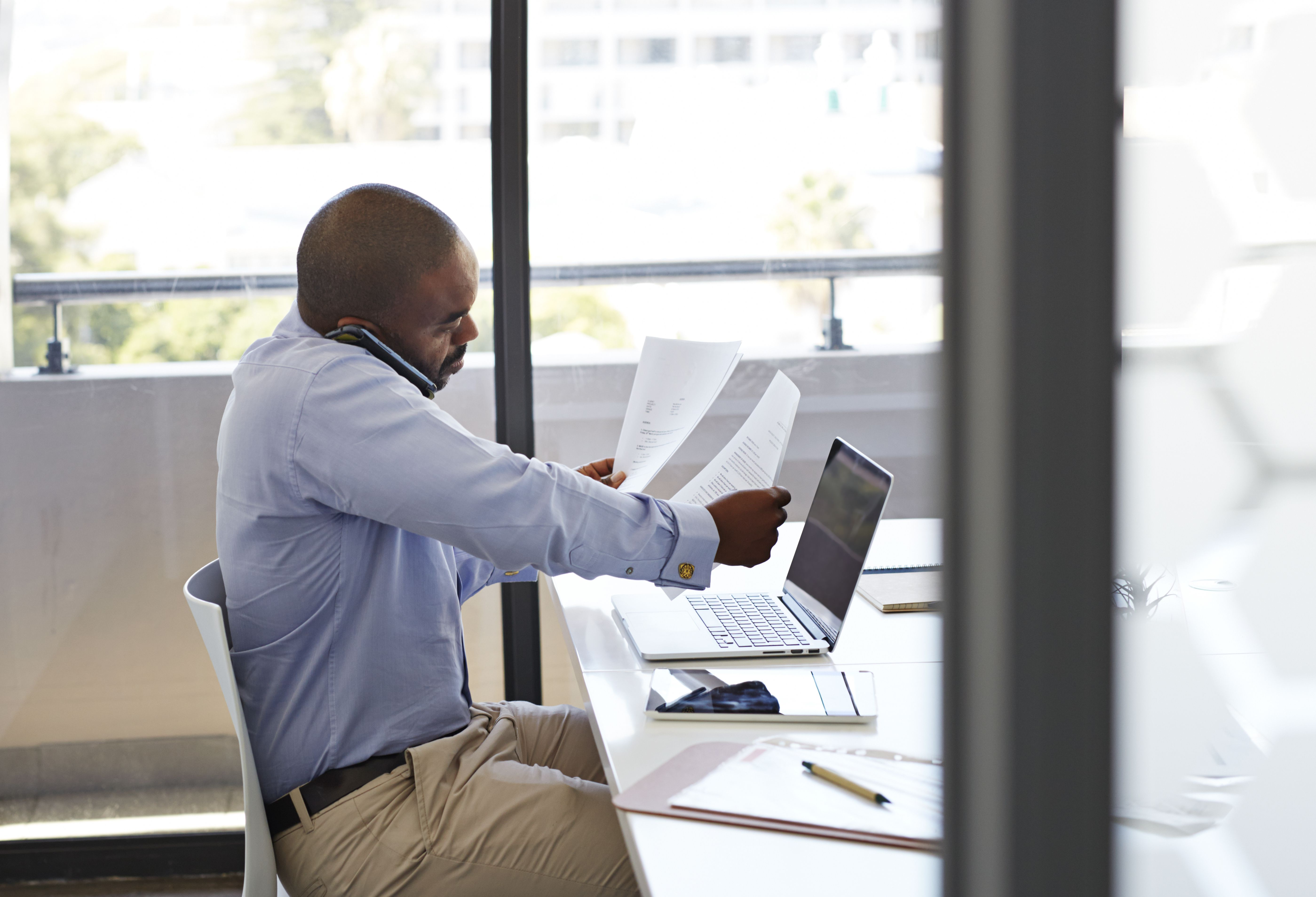 Businessman on phone and looking threw papers