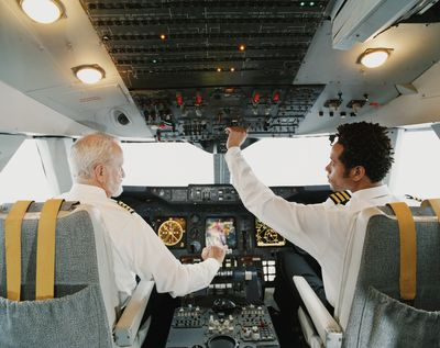 Pilots Sitting in the Cockpit, Adjusting the Controls