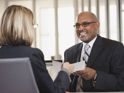 Smiling man exchanging a piece of paper with a woman seated across from him.