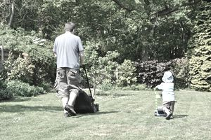 Father and son mowing
