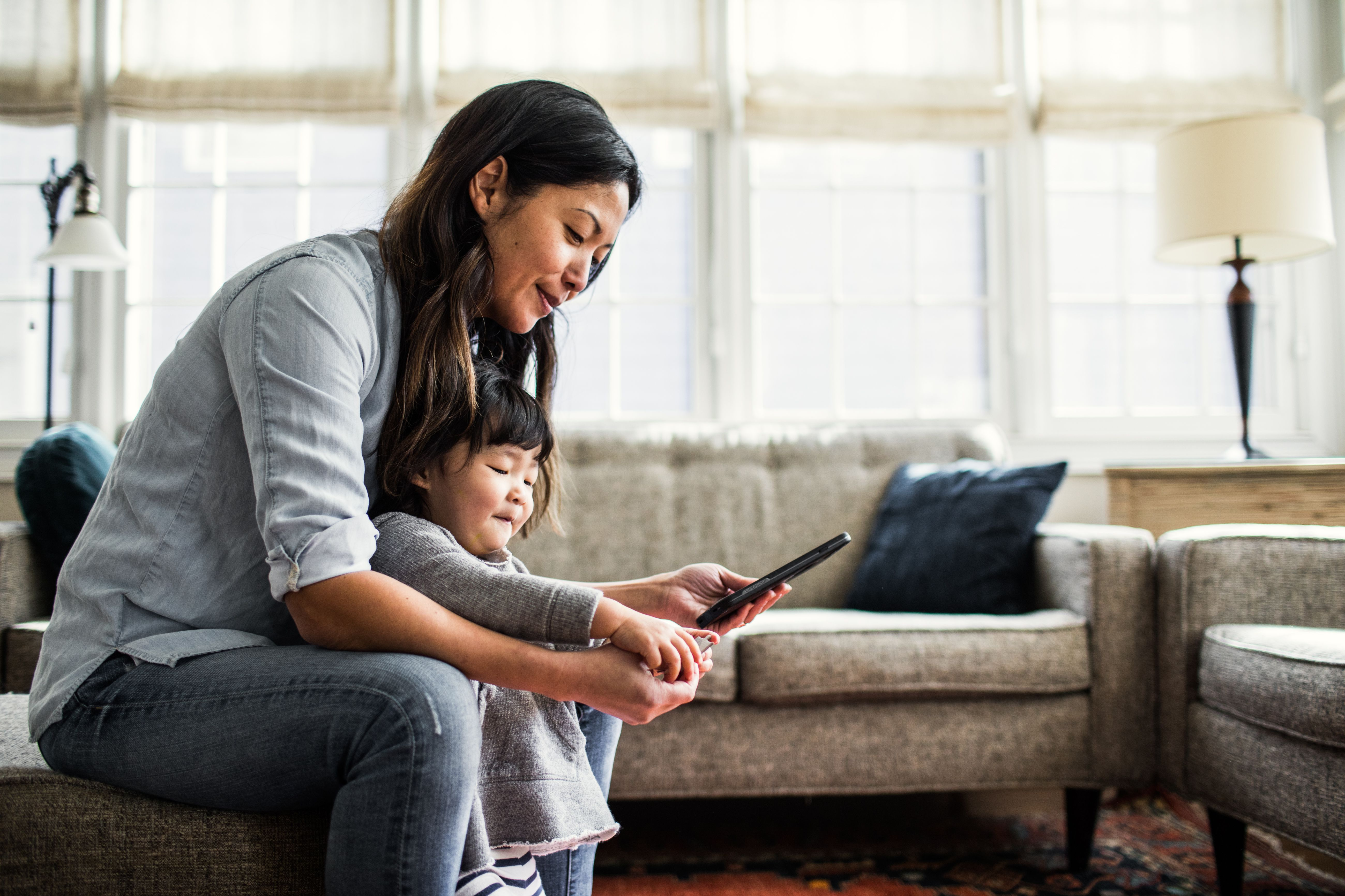 Mother using smartphone to log in to work with children present