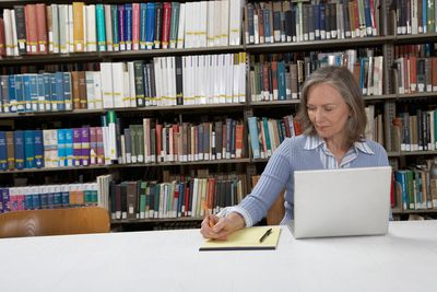Mature woman at library table, using laptop and writing notes