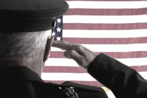 Senior Veteran Man in Military Uniform Saluting American Flag