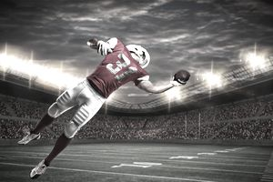 a football player reaching to catch a ball