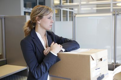 Woman with moving boxes in office, thinking