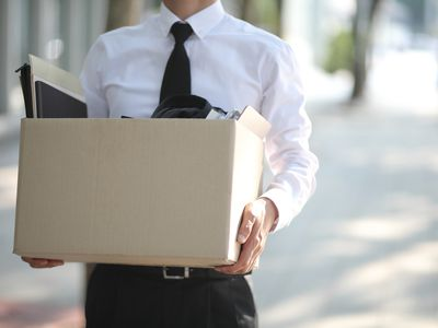 Male employee carrying box of his belongings home after being laid off
