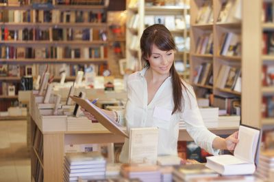Woman in book store looking at advertising and business Books