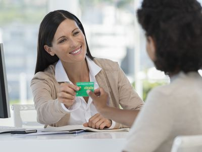 Woman handing insurance information to other woman