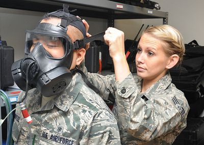 Air Force bioenvironmental engineer teaches the correct way to wear a gas mask on a volunteer.