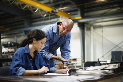 Female manager and male worker talking at desk in factory