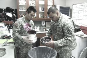 Army food inspectors putting cans of food in the trash.