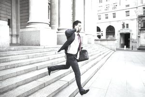 A lawyer running down courthouse steps on his cell phone
