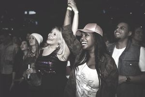 Happy, exuberant millennial women friends dancing at music concert in nightclub