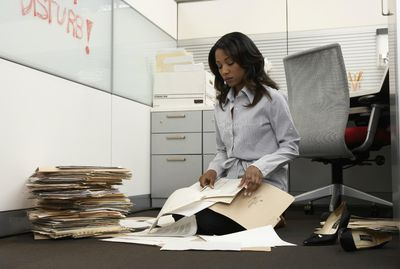 Businesswoman working on office floor surrounded by files