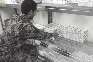 A soldier stacks items on a shelf.