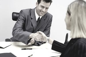 a man in a business suit shaking hands with a woman in a business suit