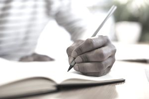Mans hand drawing in a notebook