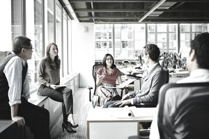 Five employees sitting in circle talking
