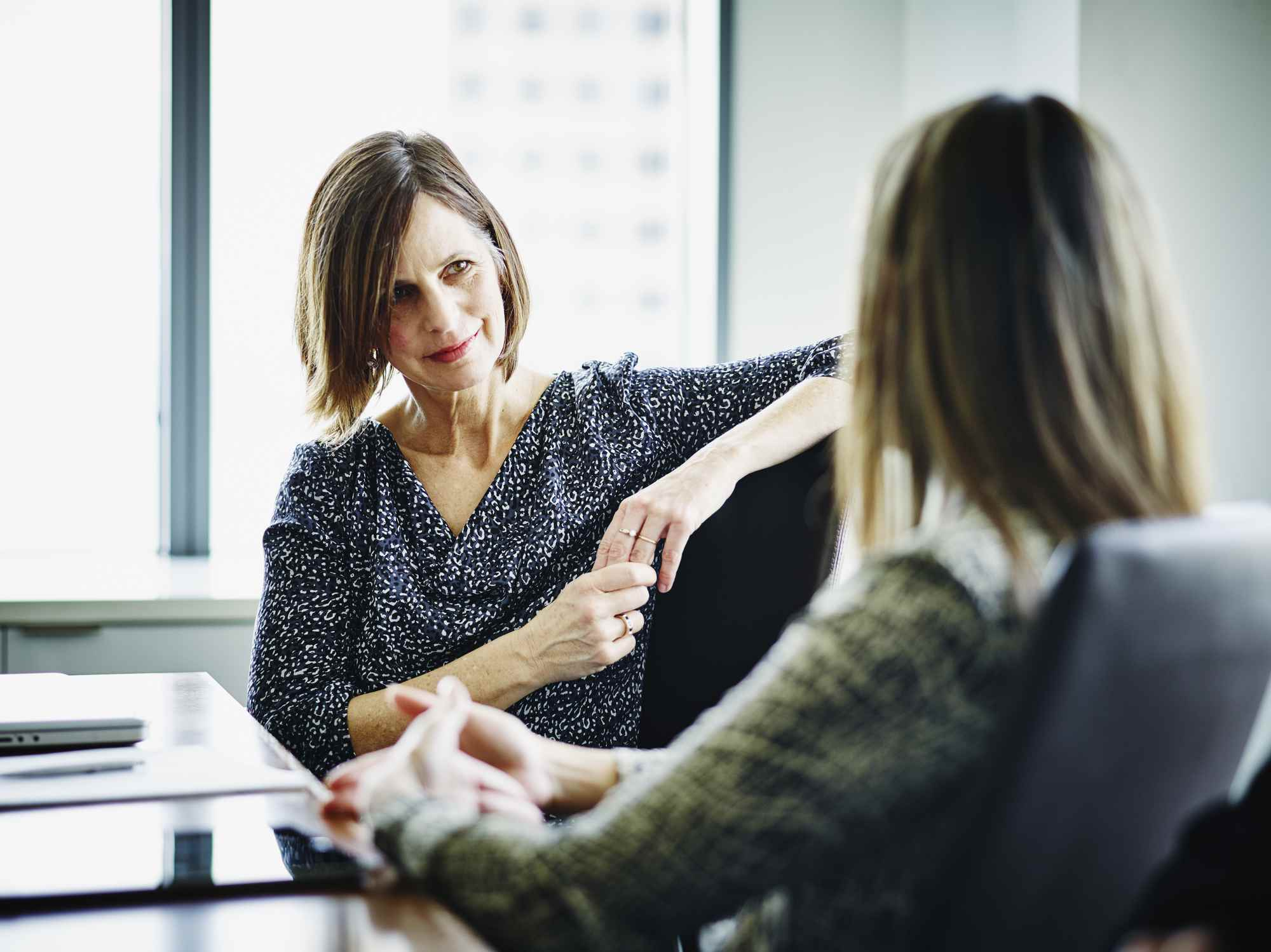Woman sitting in her boss's office explaining her reason for resigning