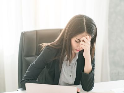 Stressed worker with her head in her hands at her office desk experiencing anxiety
