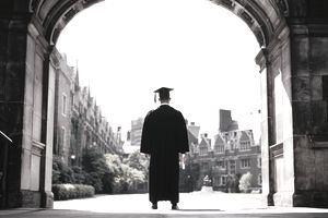 College graduate standing in archway of university