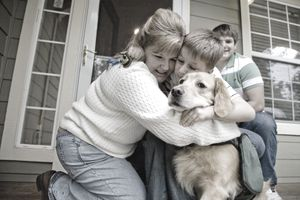 Special-needs child hugging sibling and dog on front porch of a home.